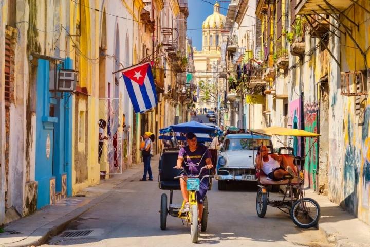 Bici taxis y auto antiguo en una calle de la Habana traslados en Cuba