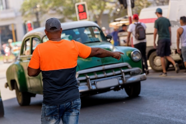 hombre-en-la-calle-solicitando-servicio-de-un-auto-privado-traslado-en-cuba-para-cubanos