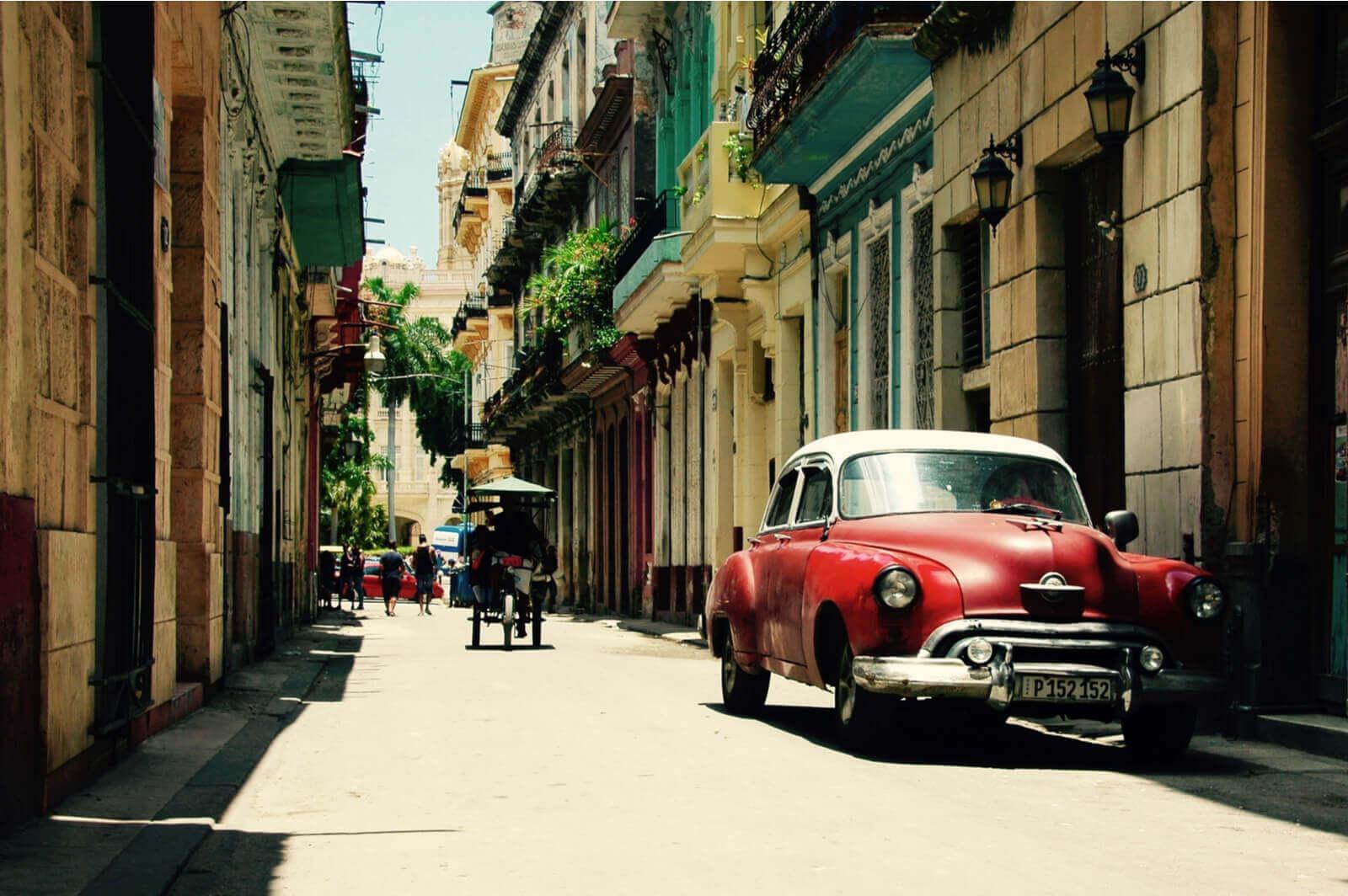 Oldtimer en fietstaxi in straatje Havana, Cuba